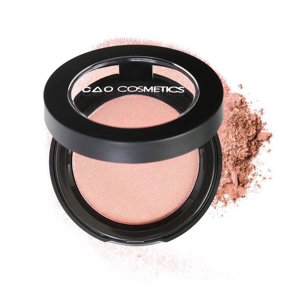 "Round Matte Black Component, clear round top window, filled with compressed round powder blush shade in ""Goddess"" on top of loose powder swatch."