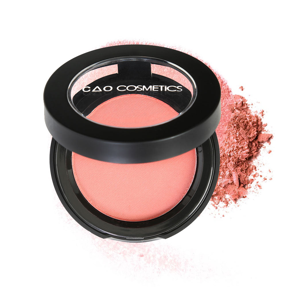"Round Matte Black Component, clear round top window, filled with compressed round powder blush shade in ""Just Peachy"" on top of loose powder swatch."