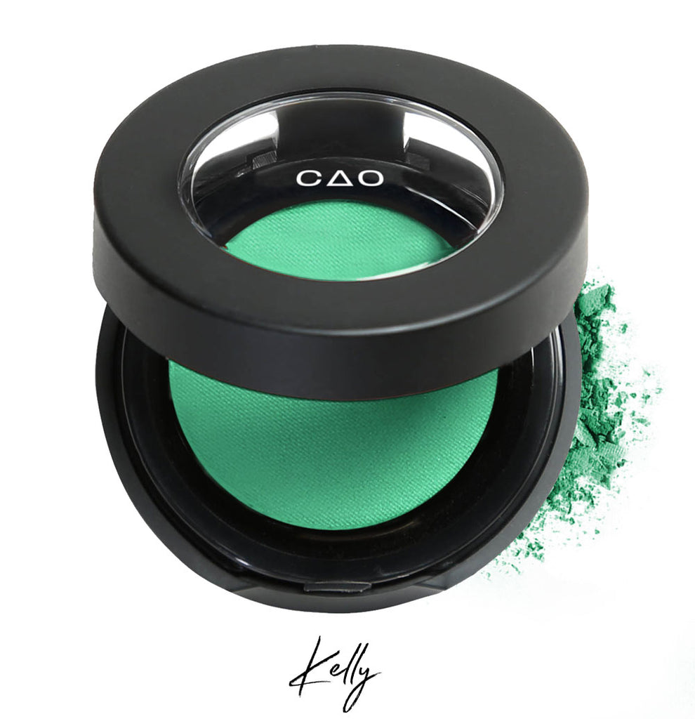 "Semi- open eyeshadow compact with light neon green eyeshadow in shade ""Kelly"" compressed powder and on white background with loose eyeshadow powder on white.."