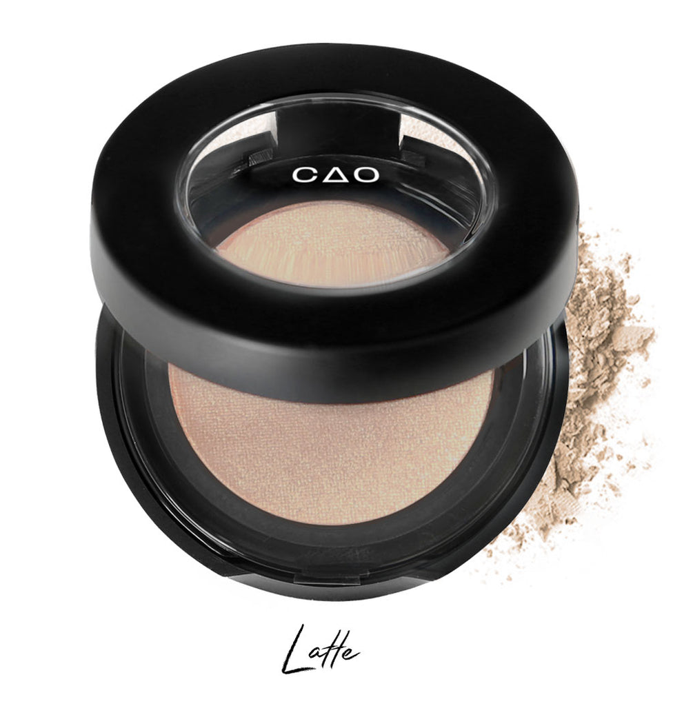 "Semi- open eyeshadow compact with light nude eyeshadow in shade ""latte"" compressed powder and on white background with loose eyeshadow powder on white.."