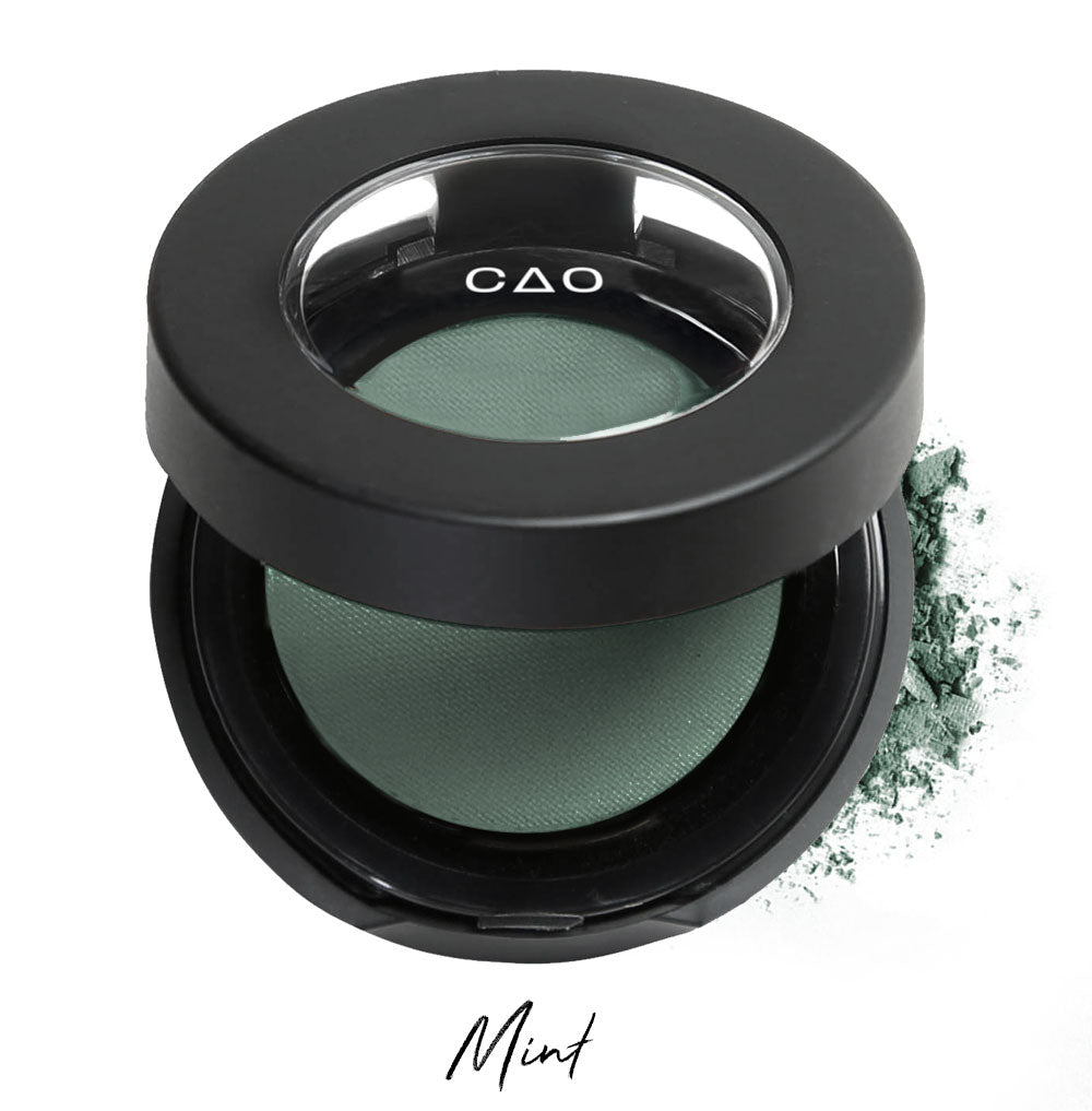 "Semi- open eyeshadow compact with desaturated green eyeshadow in shade ""mint"" compressed powder and on white background with loose eyeshadow powder on white.."