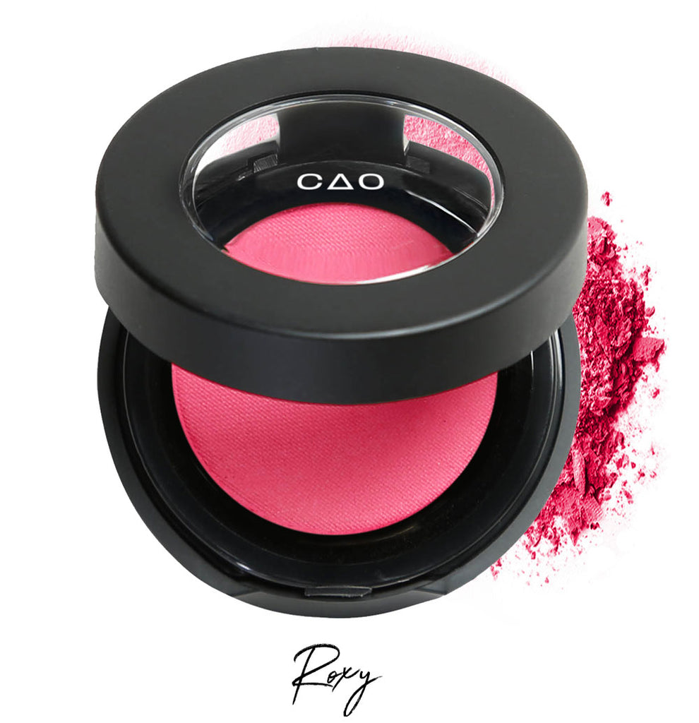 "Semi- open eyeshadow compact with neon pink eyeshadow in shade ""Roxy"" compressed powder and on white background with loose eyeshadow powder on white.."