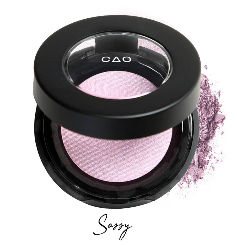 "Semi- open eyeshadow compact with lilac colored eyeshadow in shade ""sassy"" compressed powder and on white background with loose eyeshadow powder on white.."