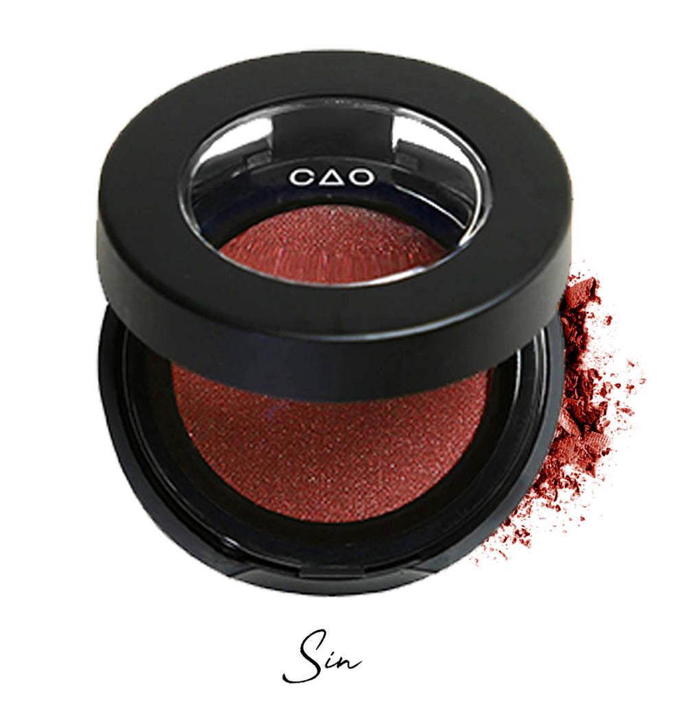 "Semi- open eyeshadow compact with dark red eyeshadow in shade ""sin"" compressed powder and on white background with loose eyeshadow powder on white.."