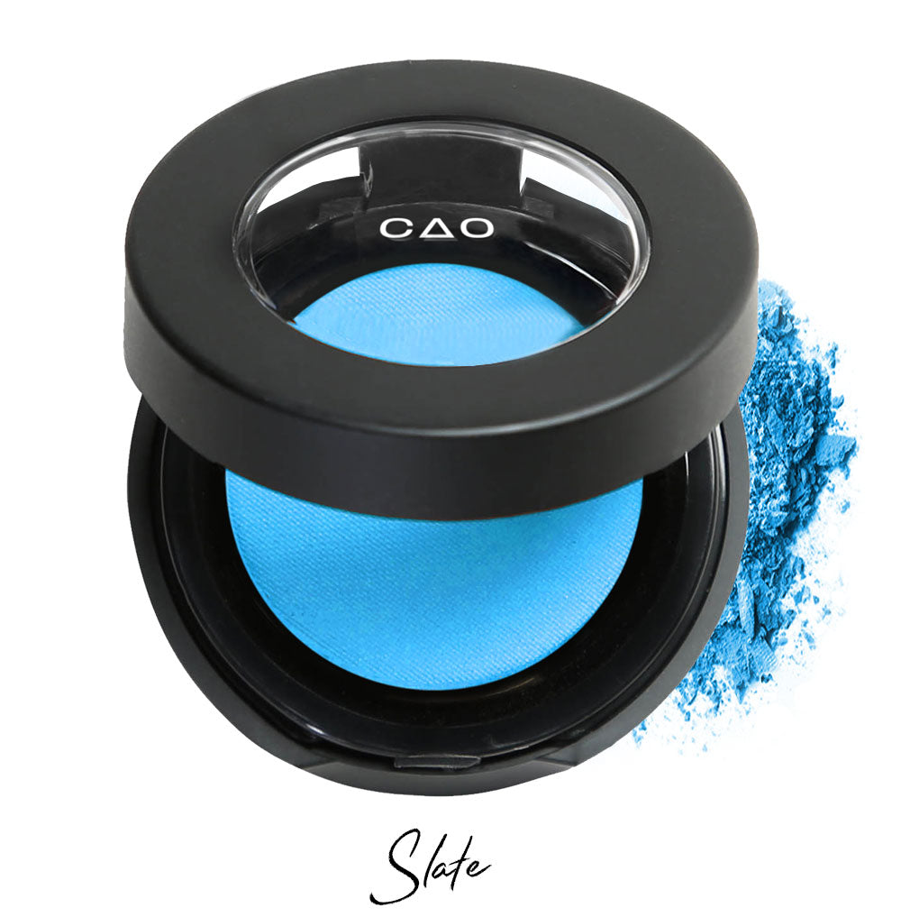 "Semi- open eyeshadow compact with light neon blue eyeshadow in shade ""Slate"" compressed powder and on white background with loose eyeshadow powder on white.."