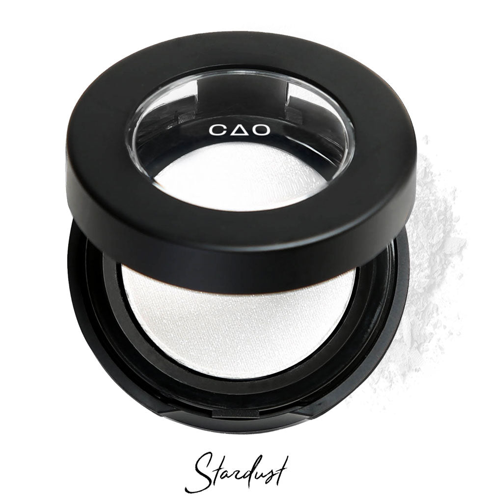 "Semi- open eyeshadow compact with white shimmer eyeshadow in shade ""stardust"" compressed powder and on white background with loose eyeshadow powder on white.."