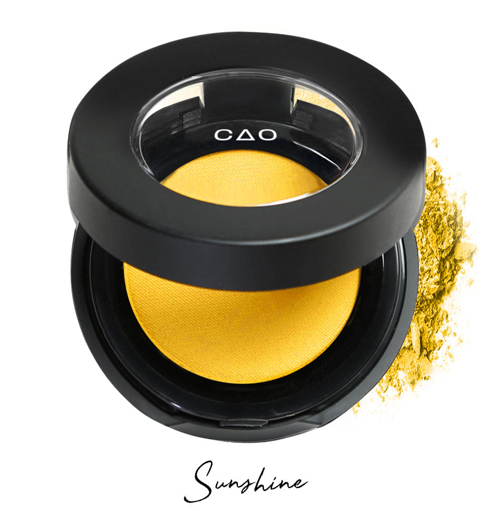"Semi- open eyeshadow compact with yellow eyeshadow in shade ""sunshine"" compressed powder and on white background with loose eyeshadow powder on white.."