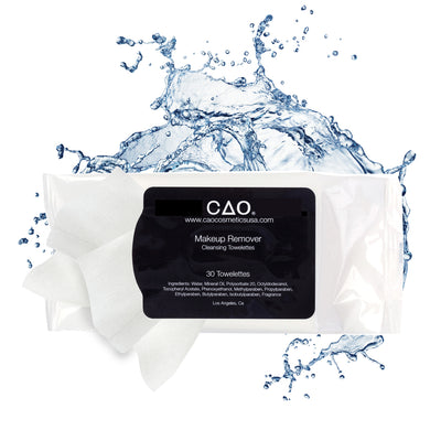 Black Sticker peeled open with a  makeup remover towelette packaged on top of a White plastic rectangle  bag on top of water splash.