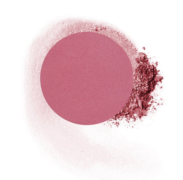 "Round compressed  powder blush refill shade in ""Diva"" on top of loose powder swatch."