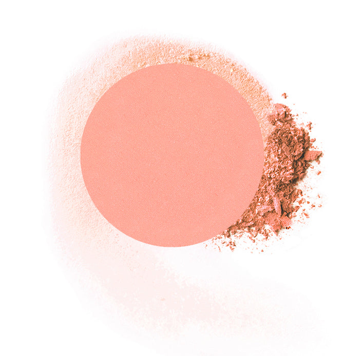 "Round compressed  powder blush refill shade in ""Just Peachy"" on top of loose powder swatch."