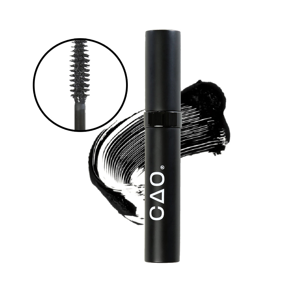 Closeup image of mascara wand tip and bristles in a black lined circle on left, on white Black matte with shiny ring mascara tube, on top of black mascara swatch on background.
