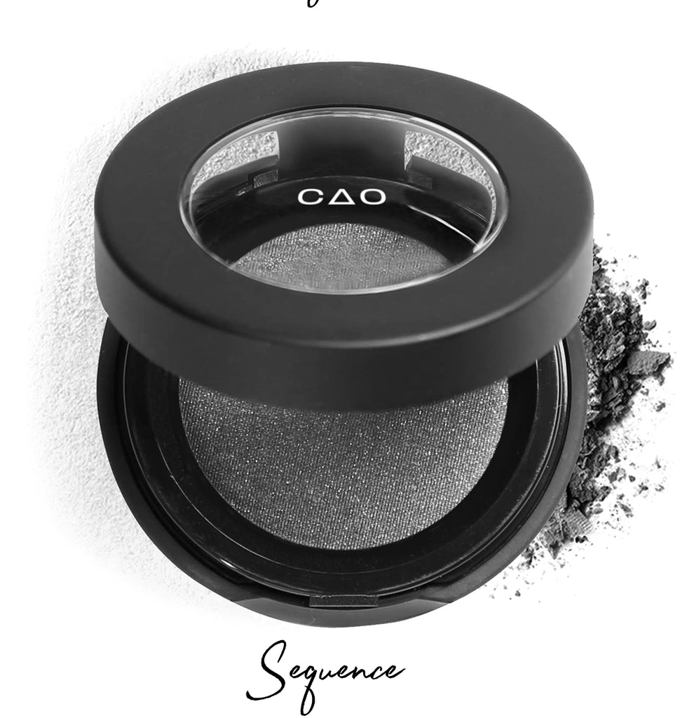 "Semi- open eyeshadow compact with silver eyeshadow in shade ""sequence"" compressed powder and on white background with loose eyeshadow powder on white."