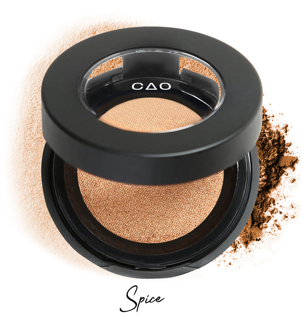 "Semi-open eyeshadow compact with light brown shadow in shade ""spice"" compressed powder and on white background with loose eyeshadow powder on white."