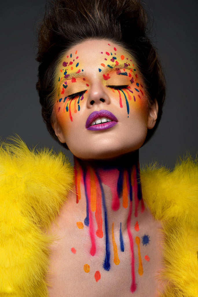 Model with airbrush makeup on closed eyes and neck, splattered and dripping colors orange, red, blue, purple, on yellow. Purple lip with pink center. Brown hair pulled back from face. Model wearing yellow fur bolero on dark gray back ground.
