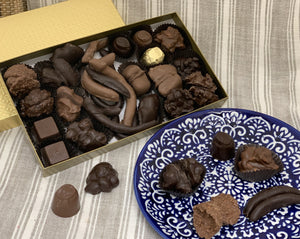 Chocolate covered fruit and chocolate covered nuts within a gold one pound box