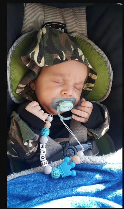 baby with pacifier clip and name on it
