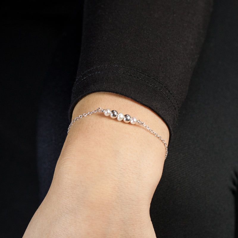 Sterling silver Celestial bracelet with freshwater pearls by Rouaida on model's wrist.