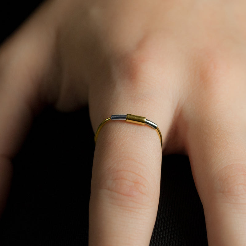 Concentric ring in sterling silver and 18ct gold on model's hand.