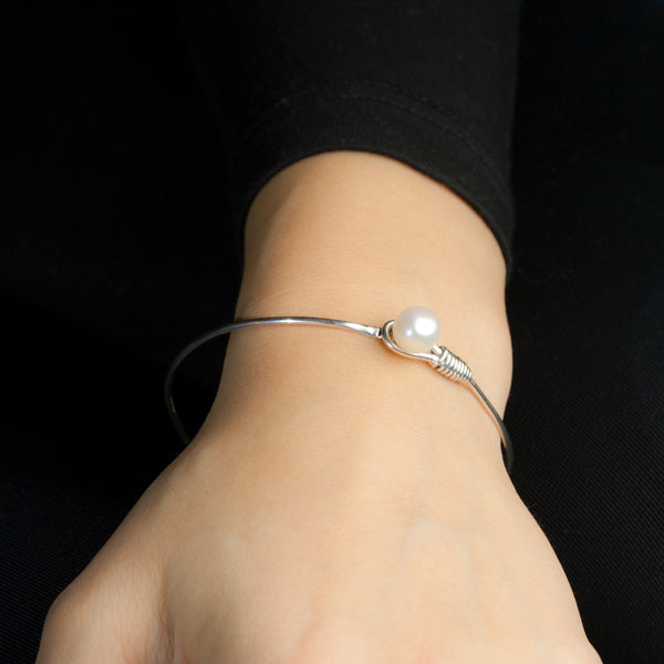 Sterling silver Grace bangle by Rouaida on model's wrist.