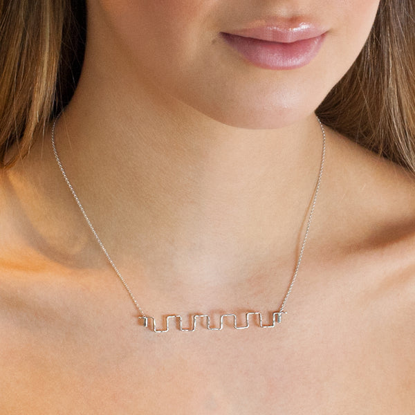 Model wearing sterling silver Iteration necklace by Rouaida.