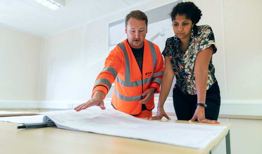 Female civil engineer discusses flood risk management with colleague