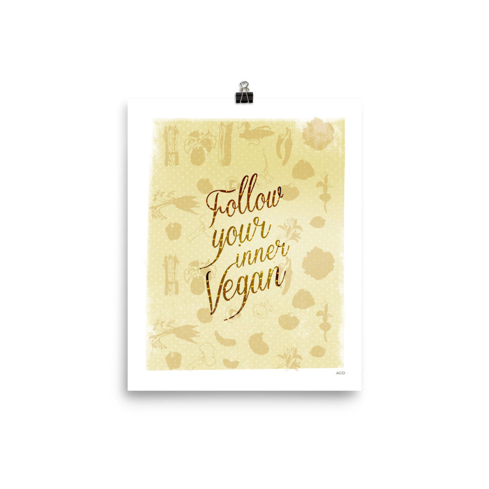 Follow Your Inner Vegan! This print features red handset caligraphic type with a golden vegetable background pattern printed on enhanced matte paper. Rich yellow hues bring warmth to any space. It is a museum-quality poster with vivid print made on thick and durable matte paper designed with a hand-drawn veggie pattern. Featuring rich browns, yellows and warm tones, this is a statement in any room.