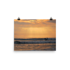 This photo captures a surfer riding a wave during an orange and lavender sunset at the Santa Monica Pier, California, USA. The golden rays shine through the glowing cloud cover which illuminates the surfer in rich yellows. This poster has a partly glossy, partly matte finish and it'll add a touch of nature, warmth, and depth to any room.