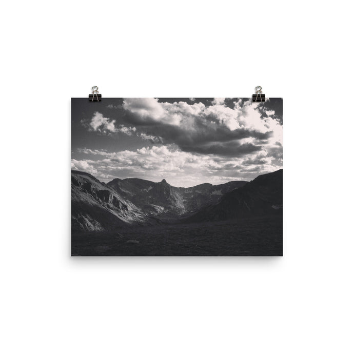 This photograph was captured in Rocky Mountain National Park, Colorado. It is a black and white image of the immaculate mountain range and features rich black shadows and white cliffs. Brilliant white clouds extend deep into the distance. This poster has a partly glossy, partly matte finish and it'll add a touch of sophistication and depth to any room.