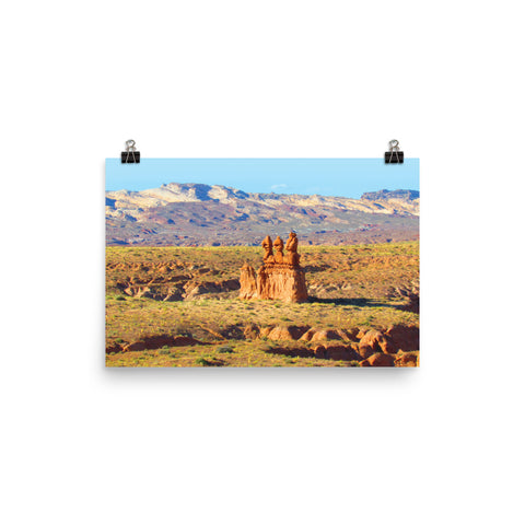 This is a photograph shows the blue, green and orange colors of the landscape of Goblin State Park, Utah. The golden red-orange sandstone rock formations look like goblins in the distance. In the distance, there is a red toned mountain range under a bright blue sky. This poster has a partly glossy, partly matte finish and it'll add a touch of sophistication and depth to any room.