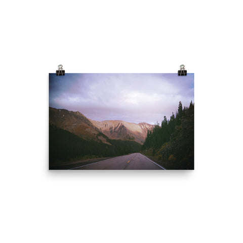 This photograph shows off a wonderous painterly blue, white and lavender sky captured in Loveland, Colorado, USA while touring the American West. The road in the center of the photo is lined with rich green western foliage and leads past an enormous mountain streaked with earthy reds, browns, and oranges. This poster has a partly glossy, partly matte finish and it'll add a touch of sophistication and depth to any room.