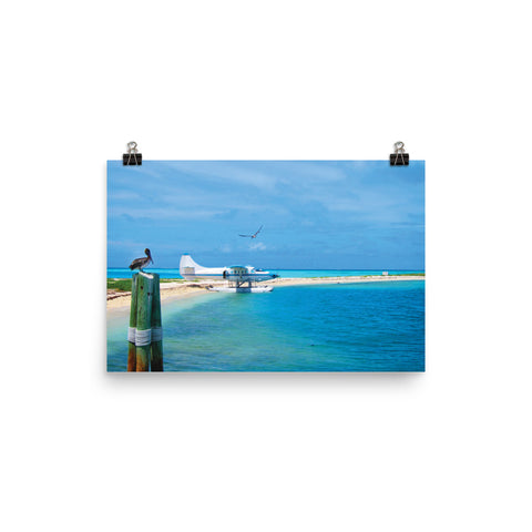 This photo captures a bright blue sky and a turquoise ocean at Dry Tortugas National Park, Key West, USA. The pristine beach landscape shows a white parked jumper plane and perching pelicans. This photograph brings a visual vacation for you to forever enjoy.