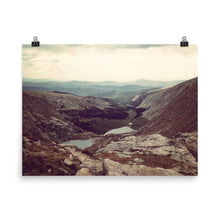 This photograph was taken at the top of Mt. Evans, Colorado at 14,000 ft. It shows off a hiking trail leading into the cascading mountains in the distance beneath an expansive bright crisp sky. This print has a partly glossy, partly matte finish featuring light yellows, blue-greens, and gray tones. It'll add a touch of sophistication and depth to any room.