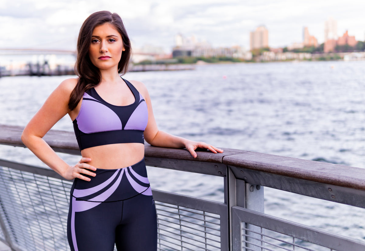 Athletic wear sports bra and workout yoga leggings with a black and purple design by horizon active worn by fitness brand model in front of a rail on the Hudson river, NY