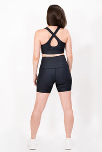 Back view of an activewear outfit in color black  that includes a criss cross strap sports bra and high waist biker shorts