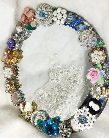 Small wall mirror with vintage jewelry findings