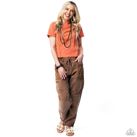 A simple vibrant colored t-shirt paired with drawstring pants and wood accessories represents the Paparazzi Dream Vacation 2021 Spring Fashion Trend.