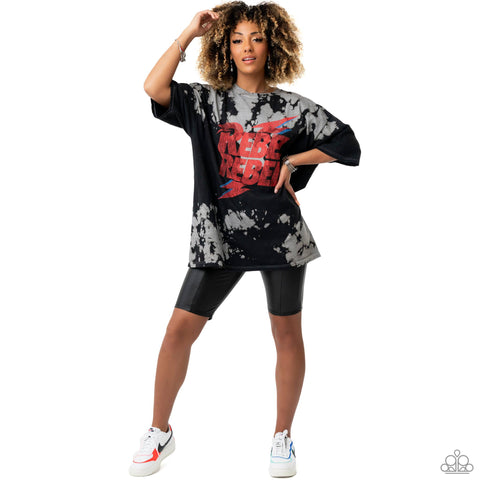 A bold graphic tee pairs with cycling shorts to create an edgy grunge look that represents the Paparazzi #NoFilter 2021 Spring Fashion Trend.