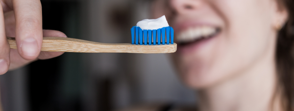 The best plastic-free alternatives - a bamboo toothbrush with blue bristles and toothpaste on top is in the foreground while a white woman smiles in the background