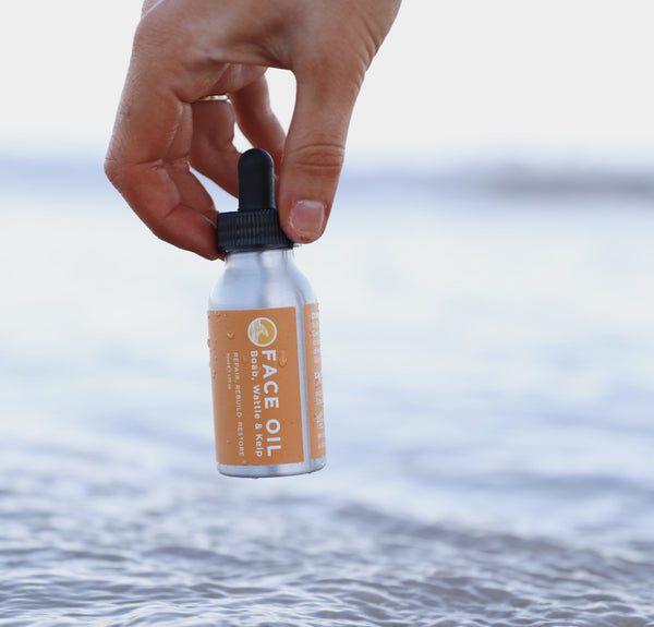 The lowdown on free radicals, antioxidants and your skin. An image of SunButter face oil being held above seawater.