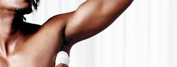The best plastic-free alternatives - a close up shot of a Black man applying roll-on deodorant under his arm