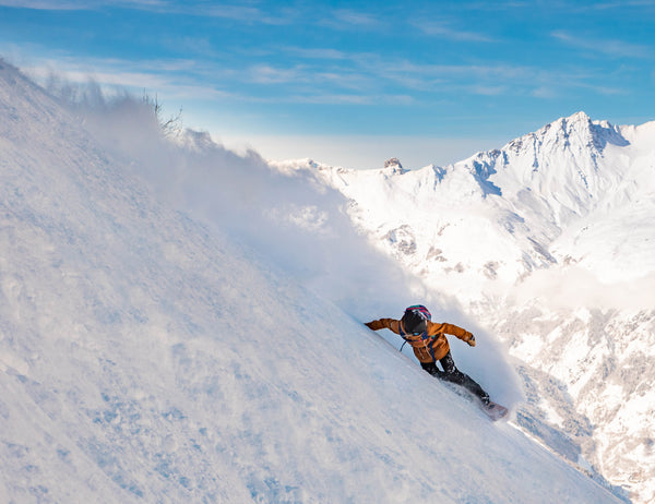Snowboarder Michaela Davis-Meehan. A figure dressed in an orange snow jacket carves some snow on the side of a mountain with a blue sky in the background.