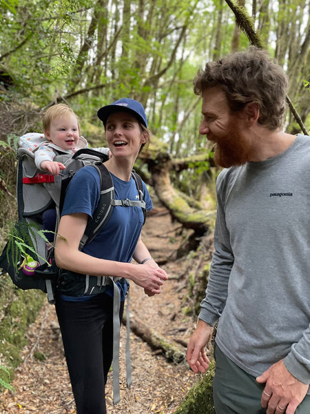 Beau and his partner walk through the bush with their infant daughter, May, in a carrier on her mother's back. All three are smiling.