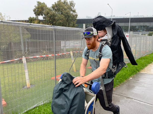 Beau Miles leaves an airport with a trolley and his infant daughter in a carrier on his back