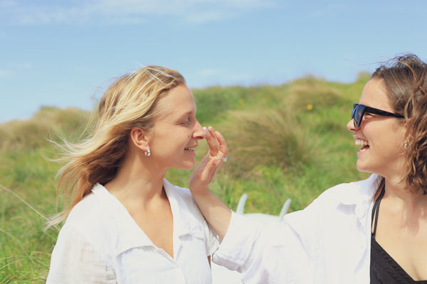 Winter skincare rituals - a white woman with blonde hair in a white shirt applies sunscreen to another white woman with brown hair who wears a white shirt and sunglasses