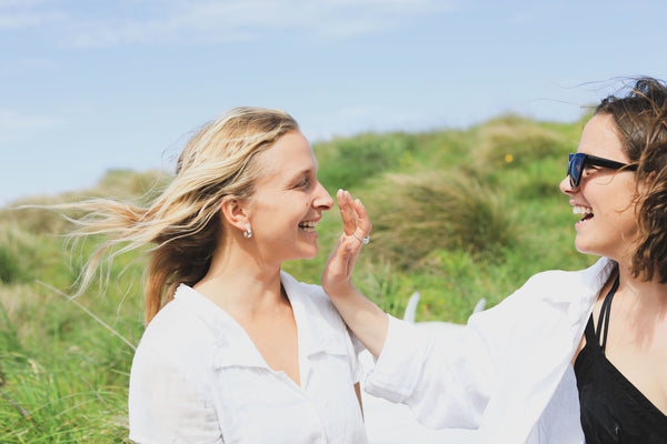 The lowdown on free radicals, antioxidants and your skin. One young woman wearing black bathers and a white shirt applies sunscreen to the face of another young woman wearing a white shirt. The background is grassy.