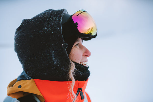 Snowboarder Michaela Davis-Meehan. A side-on close-up image of Michaela wearing red and black snow gear with a hood and snow goggles. She is smiling and there is a wavy piece of hair escaping her hood.