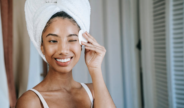 Autumn skincare regime: A woman stands smiling with a wrapped around her head as she wipes her face with a cotton round