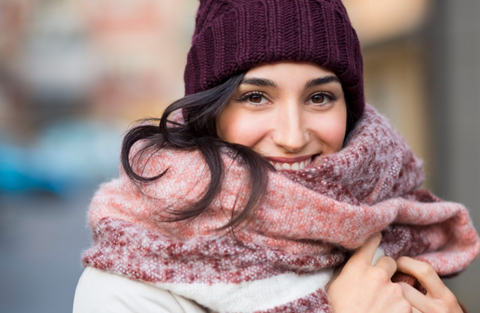 Do I need to wear sunscreen in winter? A woman is rugged up in a scarf and beanie — but wearing sunscreen!