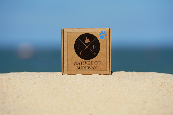 SunButter reef safe sunscreen: A box of surfboard wax sits on a patch of sand with the blue sky in the background