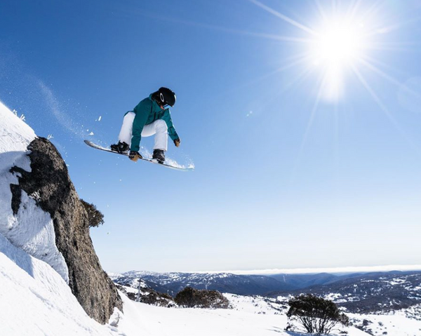 Snowboarder Michaela Davis-Meehan. A snowboarder is airborne after launching off a clifftop in the snow. The sky is blue and the sun shines brightly.